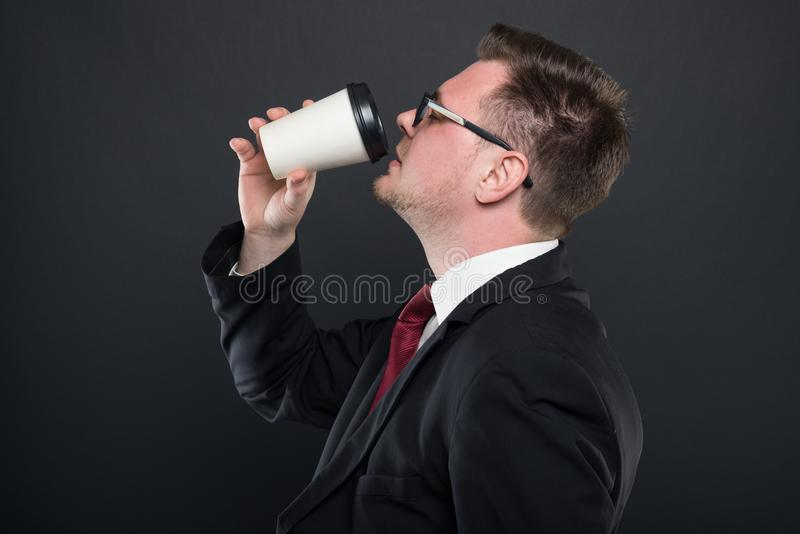 Side view of business man drinking takeaway coffee royalty free stock image