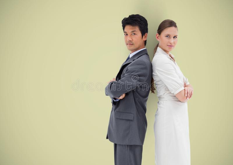Side view of business people standing with arms crossed over colored background stock images