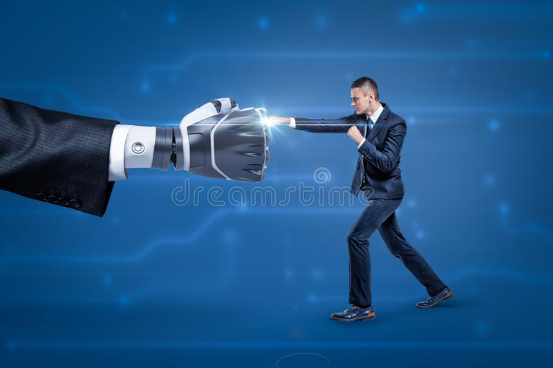 Side view of businessman fighting big robot hand, bright white spark appearing at place where they touch. stock image