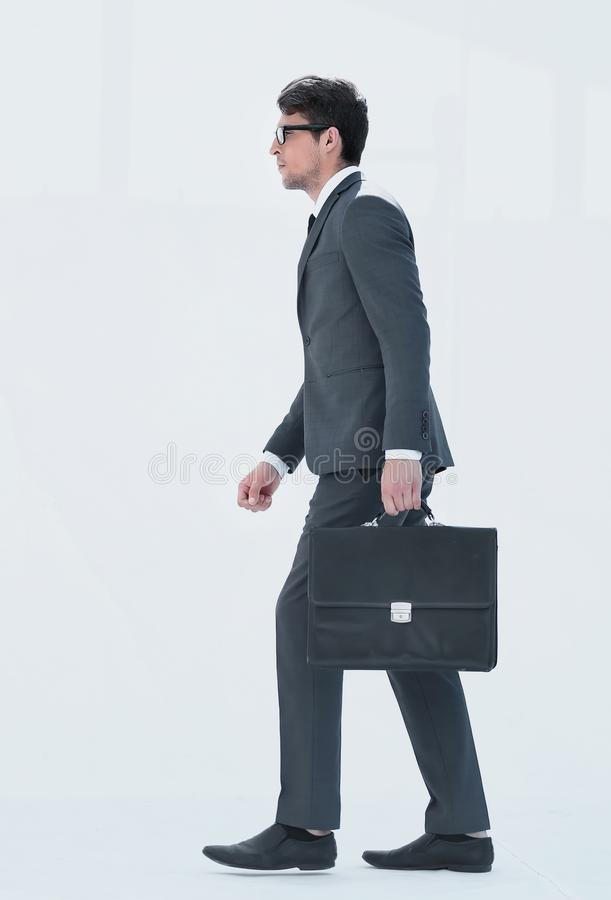 Side view. a businessman with a leather briefcase comes forward. royalty free stock image