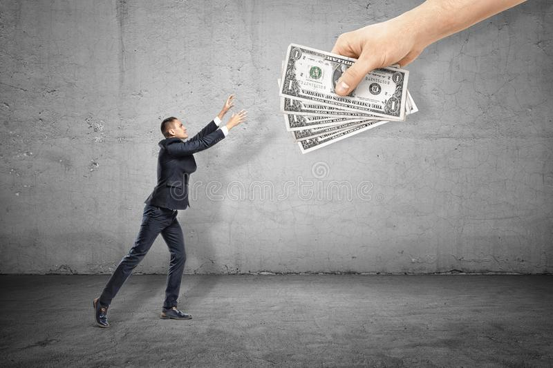 Side view of businessman raising and holding out hands to grab five banknotes held by huge human hand in right top royalty free illustration