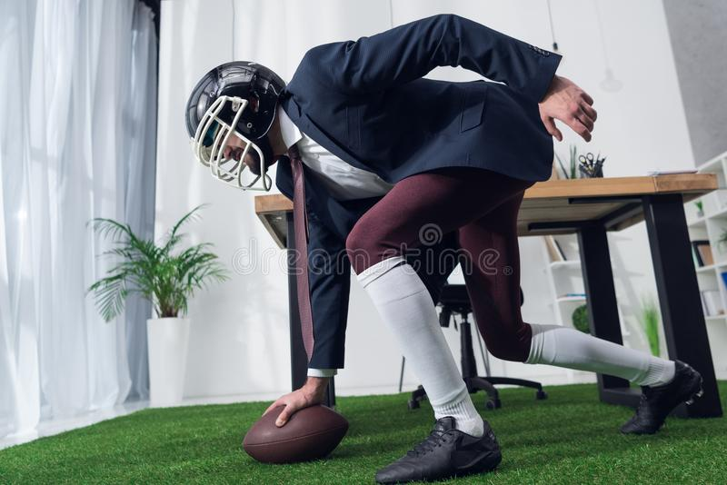side view of businessman in rugby helmet playing american football stock photo