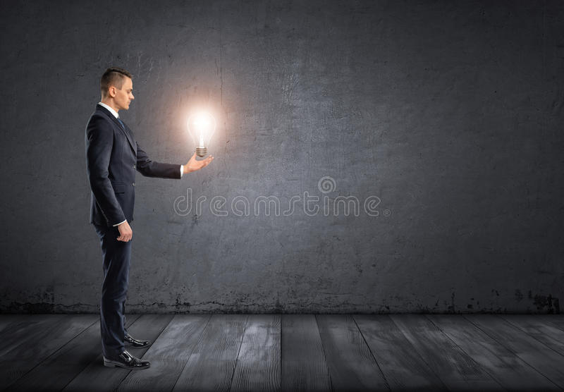Side view of businessman standing and holding glowing light bulb in his hand stock photography