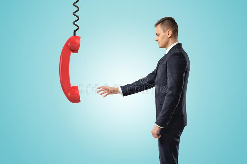 Side view of businessman standing and reaching out for big red landline phone receiver dangling down on wire from above. royalty free stock image