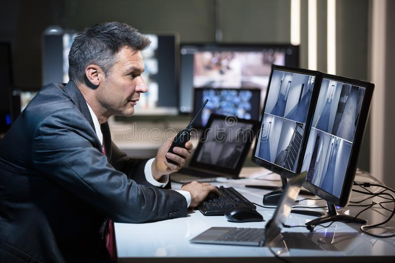 Side View Of A Businessman Talking On Walkie Talkie. Businessman Talking On Walkie Talkie While Looking At CCTV Camera Footage On Multiple Computer Screen royalty free stock photos