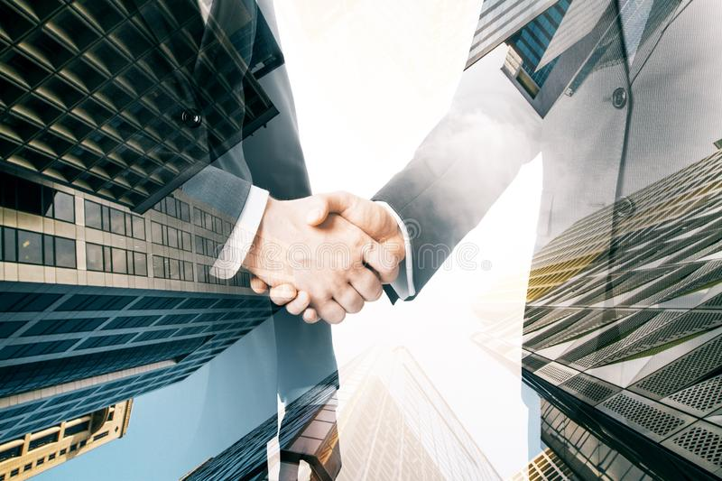 Teamwork and deal concept. Side view of businessmen shaking hands together on bright city background. Teamwork and deal concept. Double exposure royalty free stock images