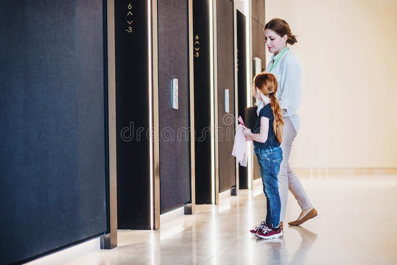 A side view of businesswoman with small daughter in office building. stock image