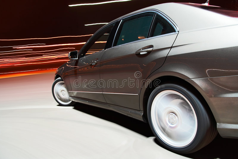 Side view of a car driving fast. In the night stock images