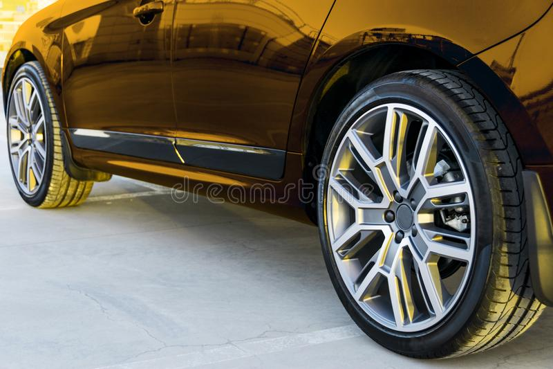 Side view of a car. Tire and alloy wheel of a modern gold car on the ground at the sunset. Car exterior details. Side view of a car. Tire and alloy wheel of a stock photography