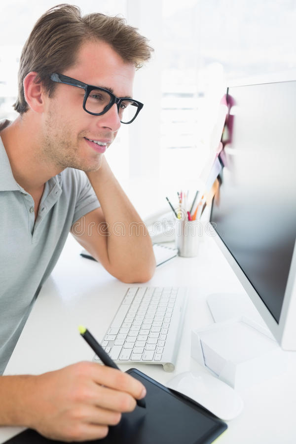 Side view of a casual male photo editor using graphics tablet stock image