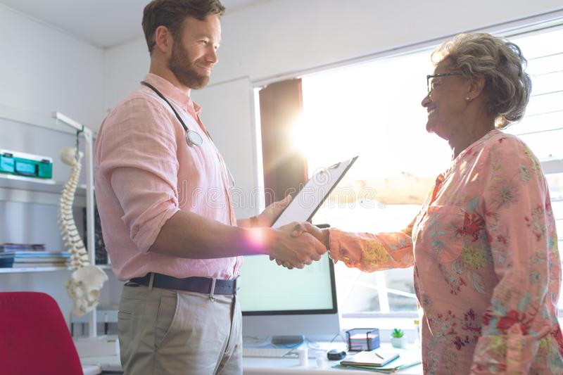 Male doctor interacting with female senior patient in clinic stock photo