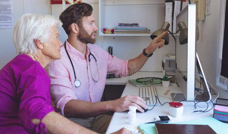 Male doctor showing medical reports on computer in a clinic room. Side view of Caucasian male doctor showing medical reports on computer to a female senior stock photos