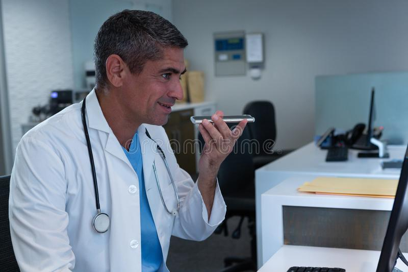 Male doctor talking on mobile phone while working on computer at desk in hospital. Side view of Caucasian male doctor talking on mobile phone while working on stock photography