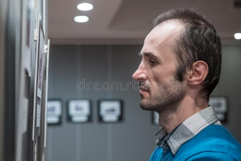 Adult Caucasian man visiting exhibition in modern art gallery royalty free stock images