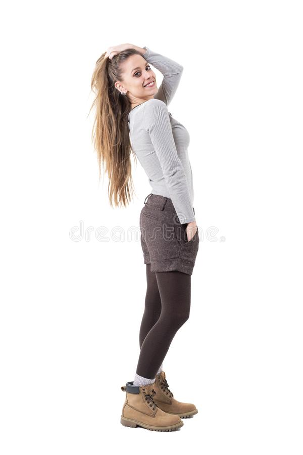 Side view of charming stylish hipster girl holding long hair in tail posing at camera. stock photography