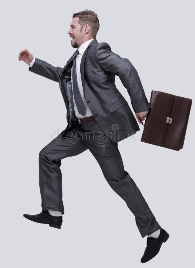 Side view.cheerful businessman with briefcase stepping forward stock images