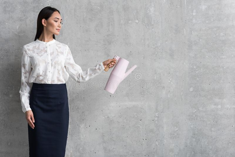 Smiling career girl keeping kettle in hand stock photos