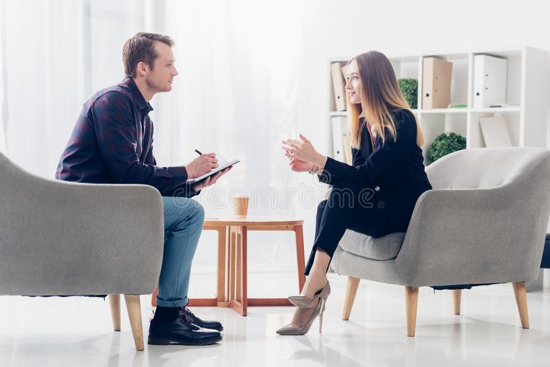 Side view of cheerful businesswoman in suit sitting on armchair and giving interview to journalist royalty free stock photos
