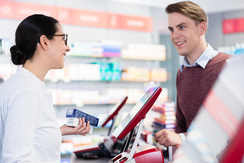 Cheerful pharmacist holding two packs of medicine giving advices stock photography