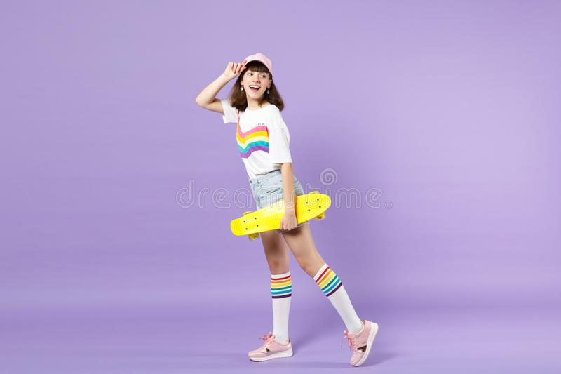 Side view of cheerful teen girl in vivid clothes holding yellow skateboard, looking back isolated on violet pastel royalty free stock photography