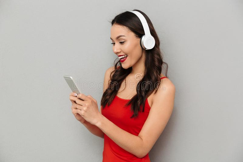 Side view of cheerful woman in casual clothes and headphones stock image