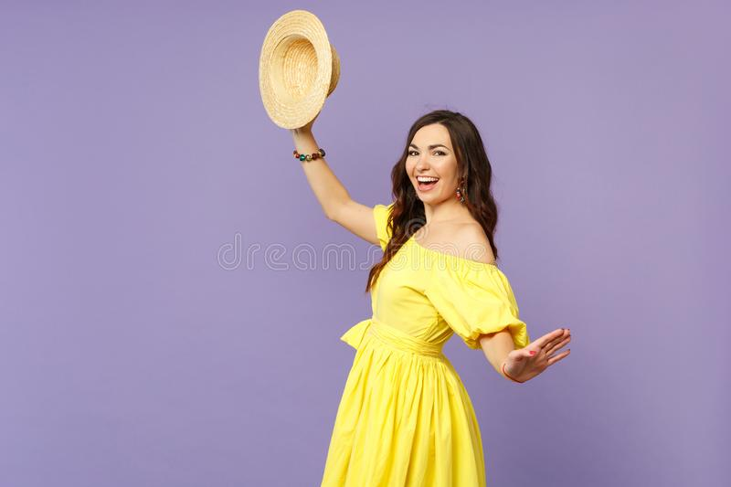 Side view of cheerful young woman in yellow dress holding summer hat spreading hands isolated on pastel violet wall royalty free stock image