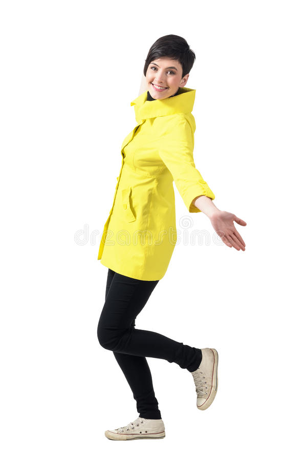 Side view of cheerful young woman in yellow raincoat running with spread arms looking at camera royalty free stock photography
