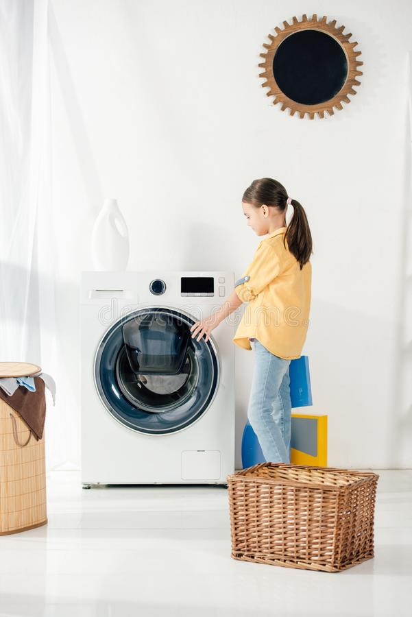 side view of child in yellow shirt near basket opening washer stock image
