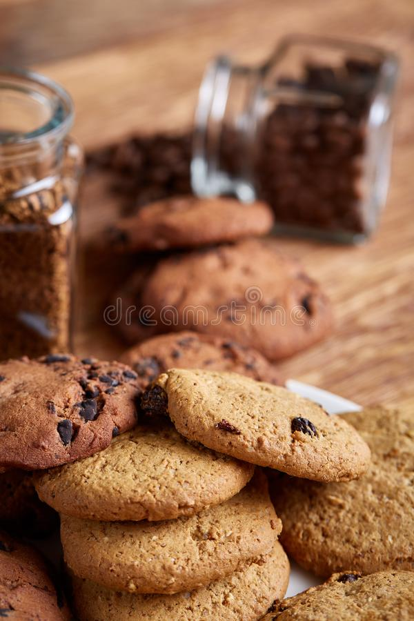 Side view of chocolate chip cookies on a wooden plate over rustic background, selective focus stock photography