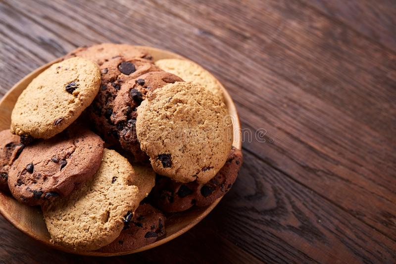 Side view of chocolate chip cookies on a wooden plate over rustic background, selective focus stock images