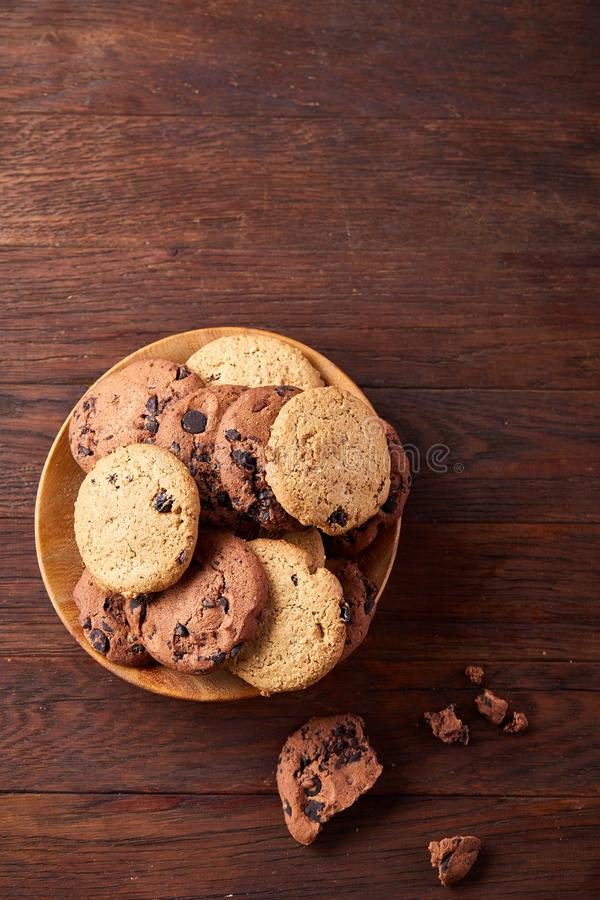 Side view of chocolate chip cookies on a wooden plate over rustic background, selective focus royalty free stock photos