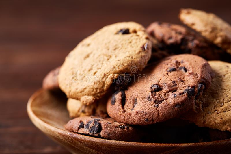 Side view of chocolate chip cookies on a wooden plate over rustic background, selective focus royalty free stock photo