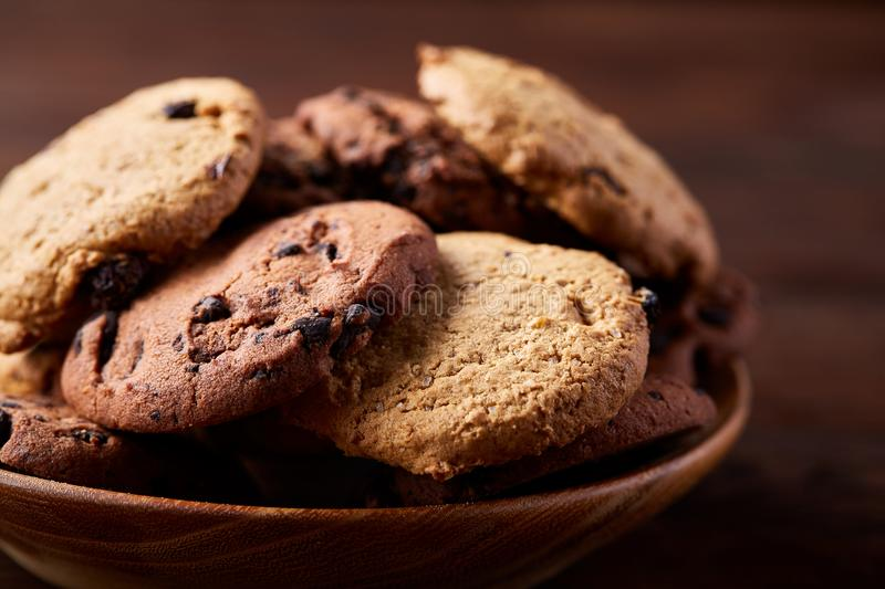 Side view of chocolate chip cookies on a wooden plate over rustic background, selective focus stock photo