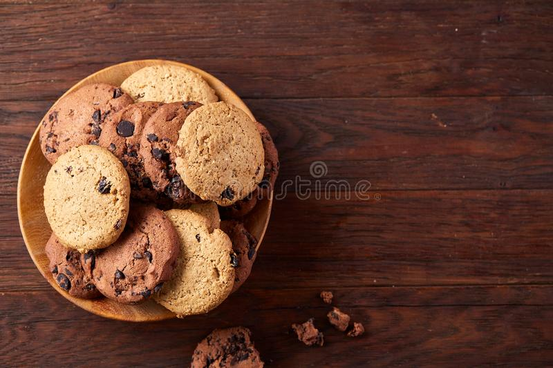 Side view of chocolate chip cookies on a wooden plate over rustic background, selective focus stock image
