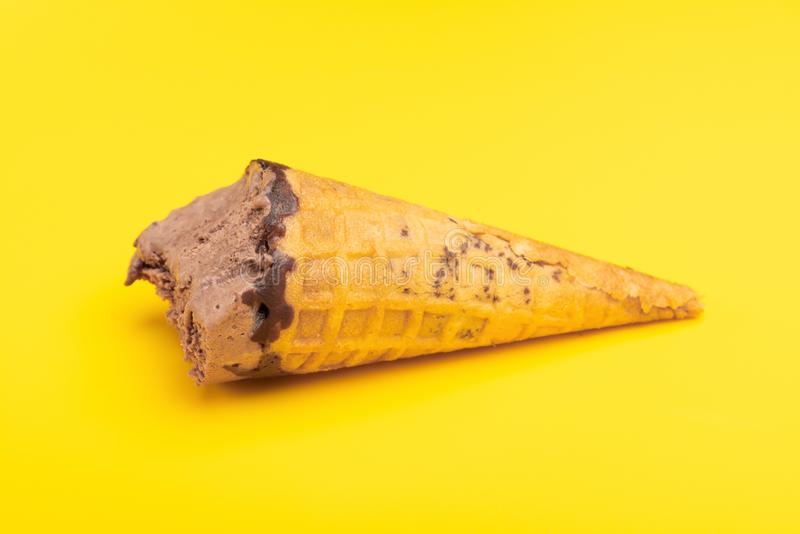 Side view chocolate flavor ice cream cone with some bites on yellow background stock photo