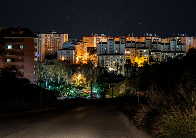 Side view of the city of marbella night, malaga. Marbella at night illuminated by the lights of the night buildings, with a road, and starry sky stock photos