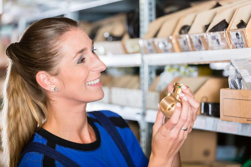 Happy blue-collar worker holding a high-quality pipe fitting accessory royalty free stock images