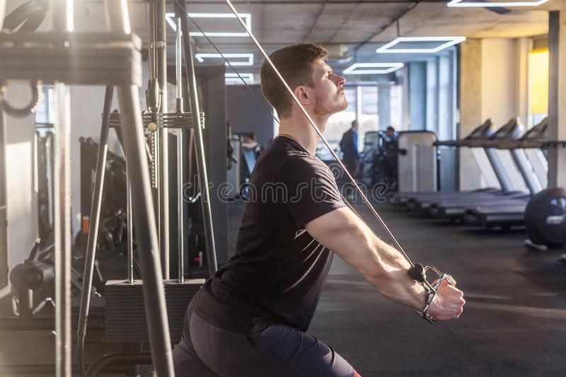 Side view close up portrait of young adult confident crossfit man standing and doing trx exercises in the gym alone, training royalty free stock photography