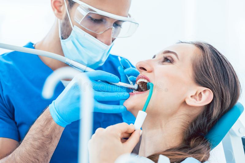 Young woman during painless oral treatment in the modern dental royalty free stock photography