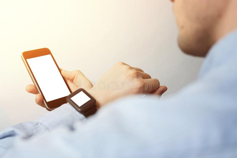 Side view, close-up of a smartphone with a blank screen and a smart watch on a male hand. Man using gadget royalty free stock photos