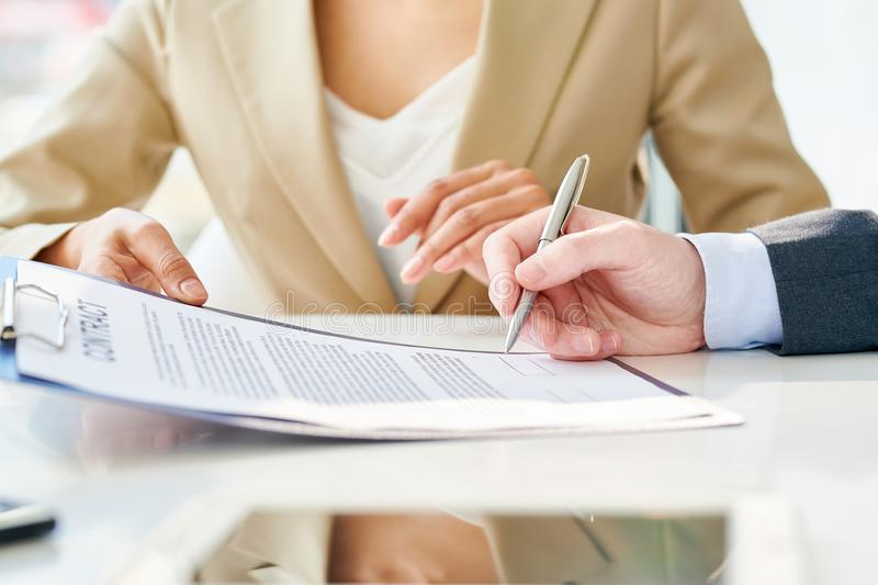 Unrecognizable Businessman Signing Contract Close Up. Side view close up of unrecognizable businessman signing contract during meeting with unrecognizable royalty free stock photography