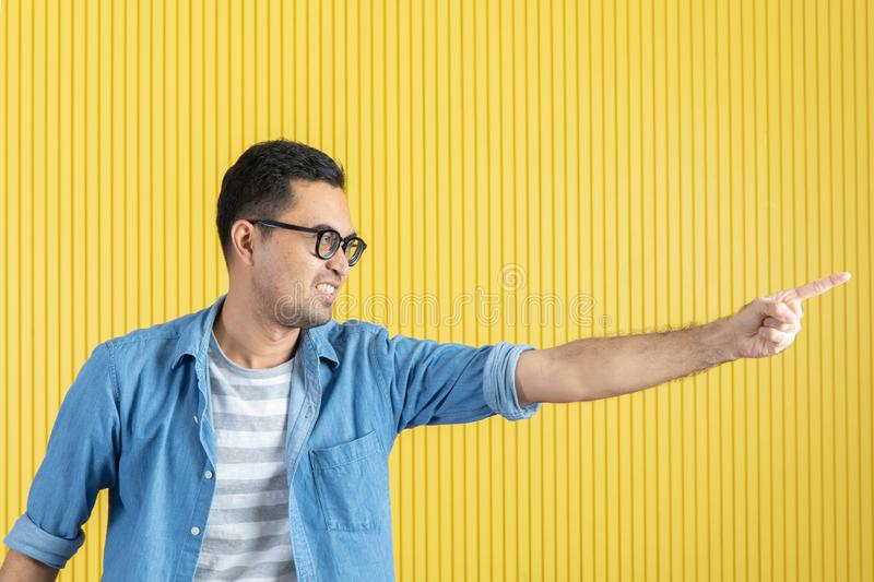 Side-view, close up of young Asian handsome bearded man, wearing eyeglasses, in denim shirt, pointing playfully to his left side, royalty free stock photography