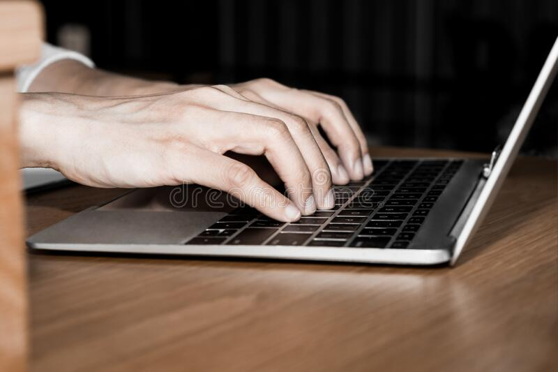 Side view and close up of young woman hands are typing on the modern laptop computer keyboard on wooden office table desktop with. Supplies for business and stock image