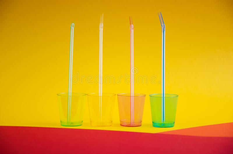 Side view of colorful empty plastic glasses with straws inside them, on multi color background stock image