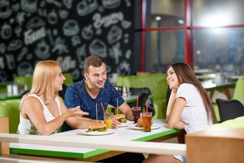 Side view of company laughing in cage. Side view of laughing company sitting in cafe and communicating. Cheerful girls and boy eating tasty burgers, drinking stock photos