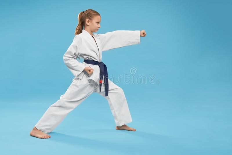 Side view of concentrated girl in kimono standing in stance. And doing karate in studio. String child looking forward and exercising on blue  background stock photo