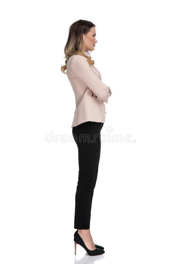 Side view of confident busiensswoman wearing high heels. Side view of confident businesswoman wearing high heels while standing on white background and waiting royalty free stock photography