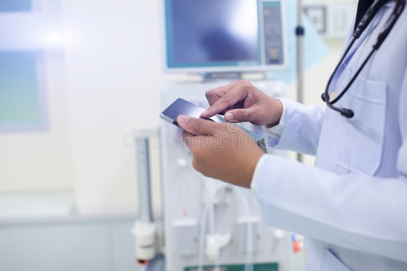 Side view of confident doctor in white medical uniform touching tablet with him finger at hospital. royalty free stock images