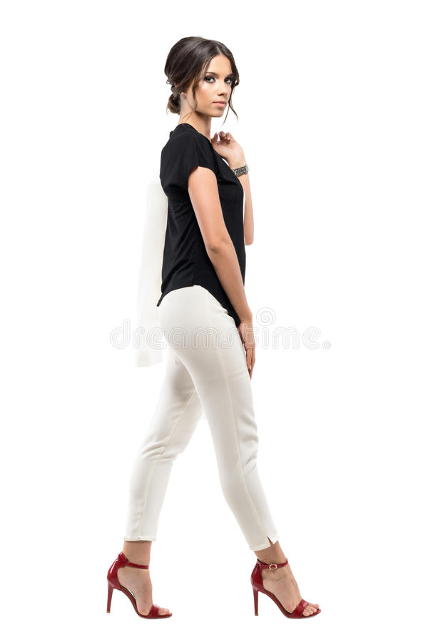 Side view of confident gorgeous business woman in suit walking and looking at camera. royalty free stock photography