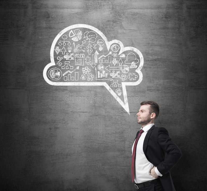 Side view of the confident man, student, who is thinking about new business concepts. Drawn cloud with business icons on t stock image